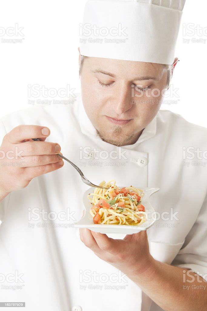 Young chef tasting a pasta dish royalty-free stock photo