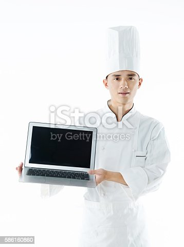 Young chef holding a laptop against white background.