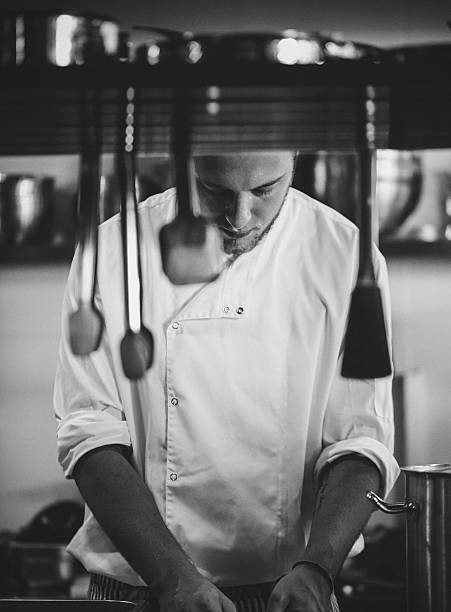 Young Chef working in a commercial kitchen. stock photo