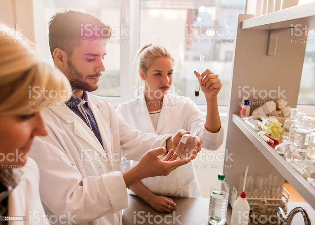 Young chemist working in laboratory with his colleagues. stock photo
