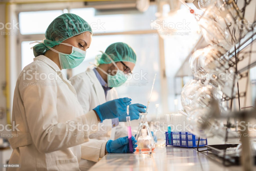 Young chemists working on chemical substances in a laboratory. stock photo