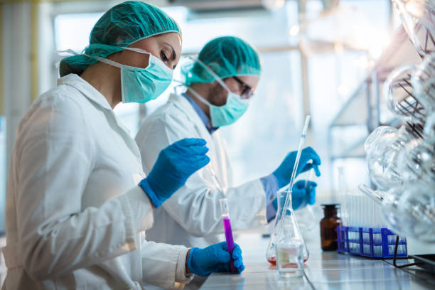 young chemists working on scientific research in a laboratory. - ricerca scientifica foto e immagini stock