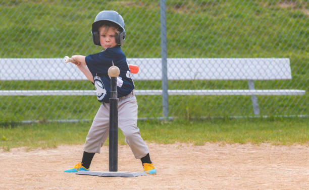 Young Child Attempting to Hit a Baseball Off of a Tee During a Baseball Game stock photo
