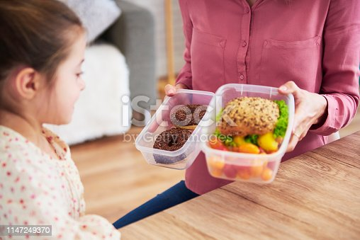 Young child choosing between healthy sandwich and chocolate donuts