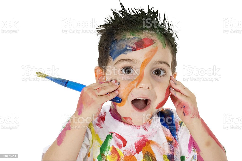 Young child covered in paint holding a paintbrush royalty-free stock photo