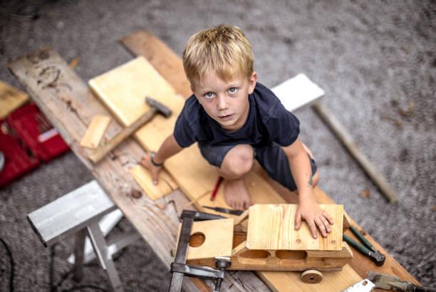 junges kind basteln eines autos aus holz - kindergarten workshop stock-fotos und bilder
