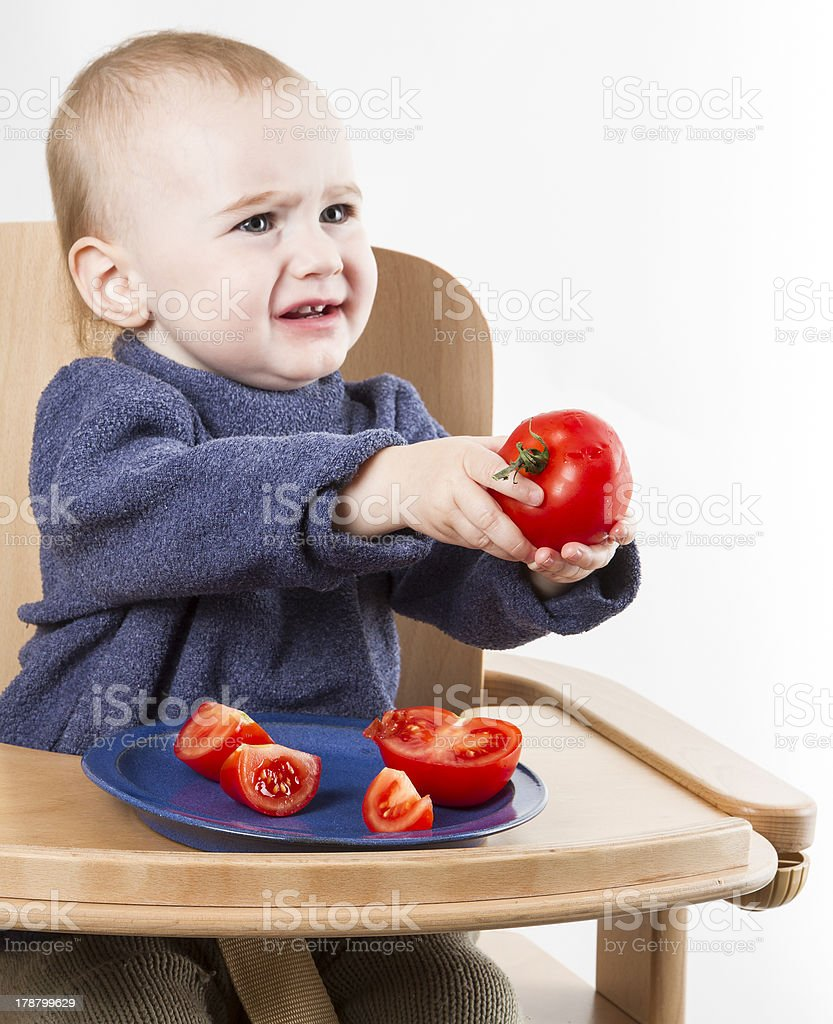 young child eating tomatoes in high chair stock photo