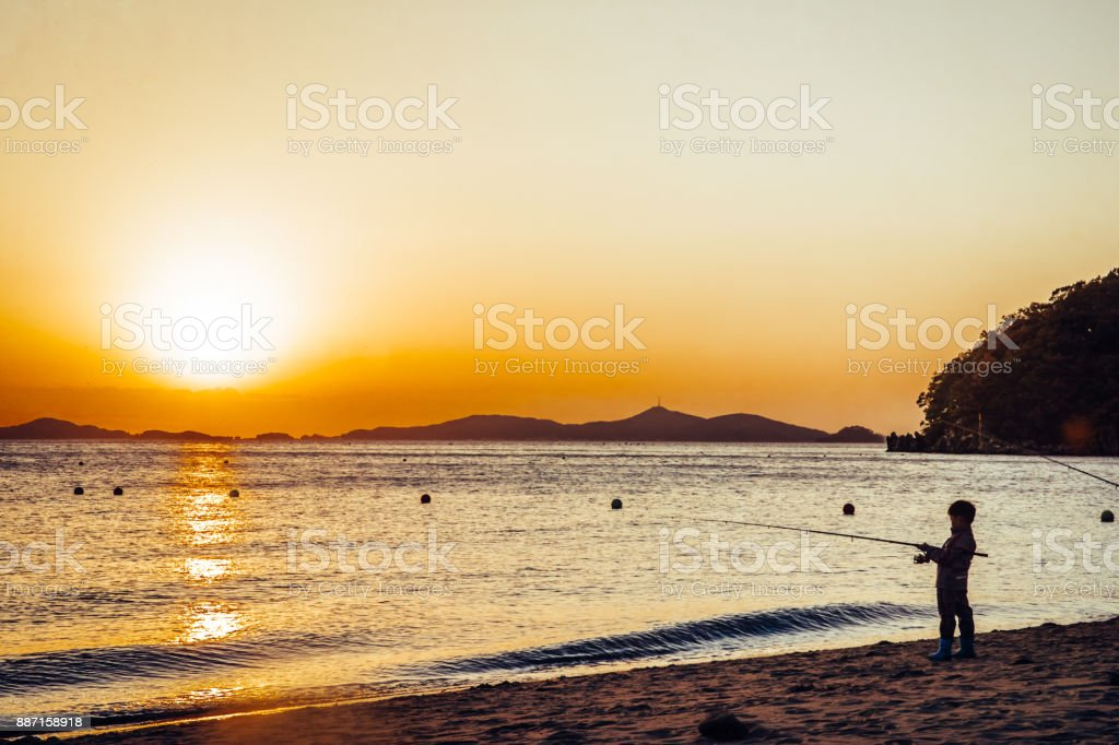 A young child fishing in the sea. stock photo