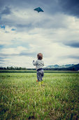 View from behind of a cute young child in gumboots standing flying a kite in a grassy green field standing holding the string watching it soar in the air above open countryside.
