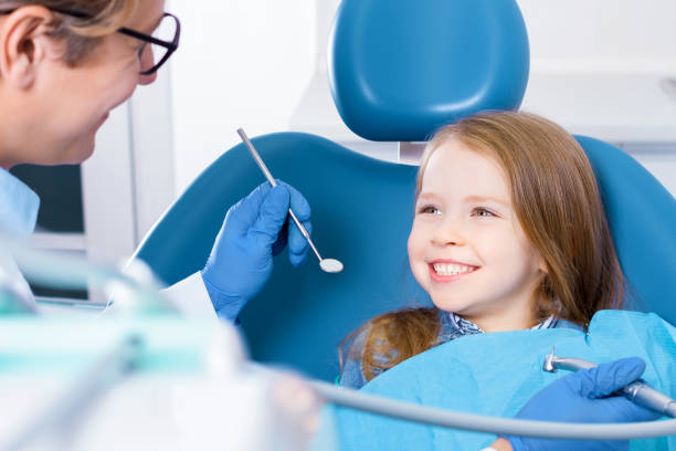 Young child girl check out teeth at dentist office stock photo
