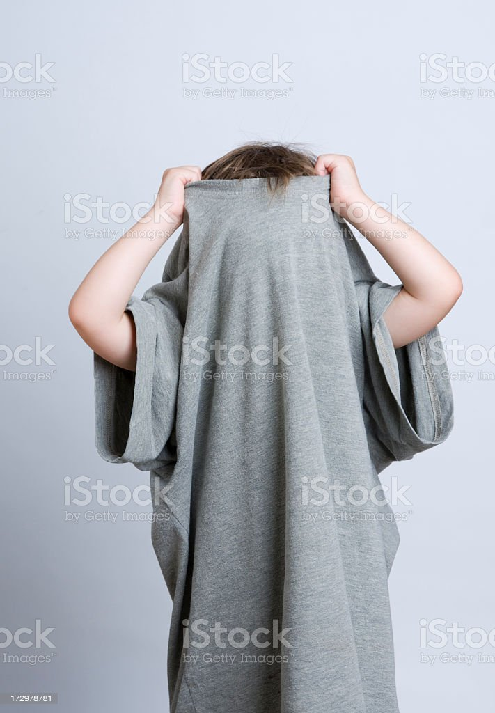 Young child hiding in Daddy's T-shirt stock photo