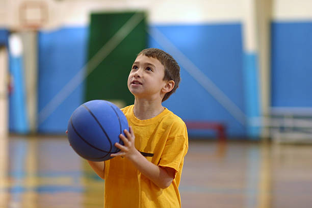 A young child holding a blue basketball stock photo