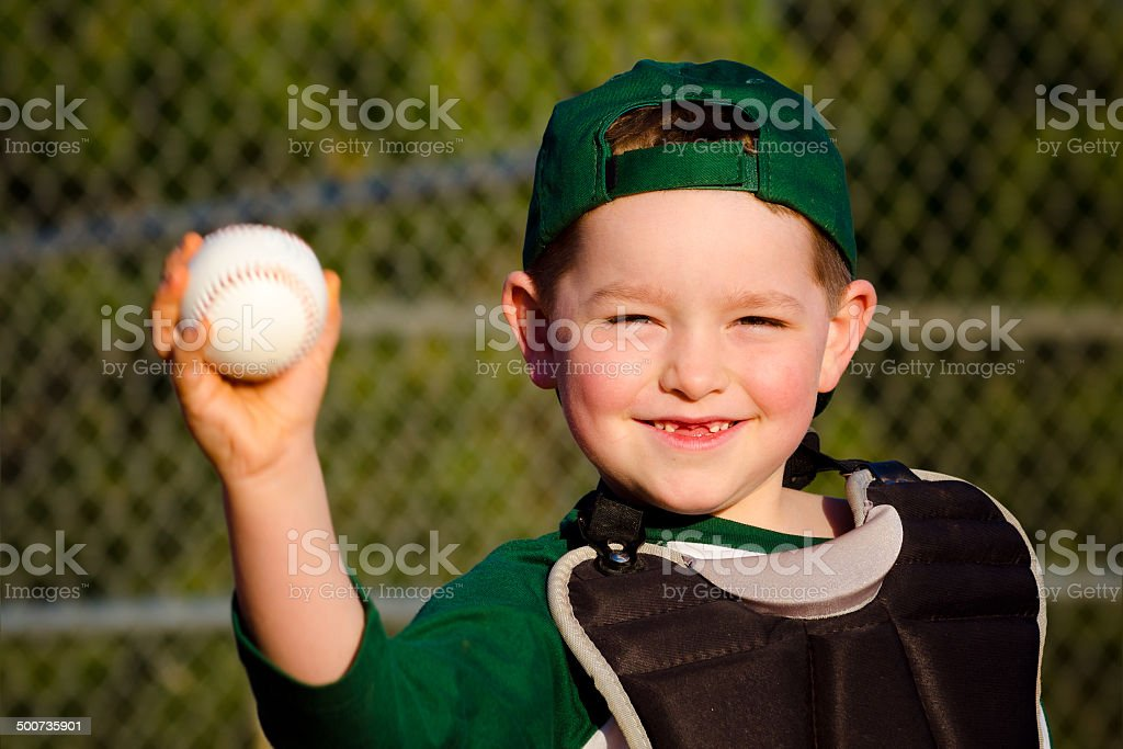 Young child in catcher's gear throwing baseball stock photo
