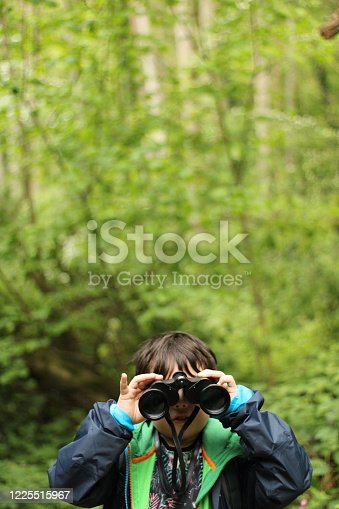 A young child in the green forest looking directly at the camera with binoculars the background is blurred for copy space