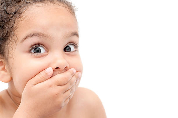 Young child looking surprised and covering mouth with hand Royalty free stock photo of 4 years old girl with her hand covering her mouth.  gasping stock pictures, royalty-free photos & images