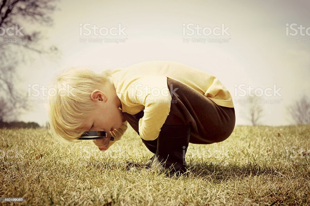 Young Child looking through Magnifying Glass stock photo