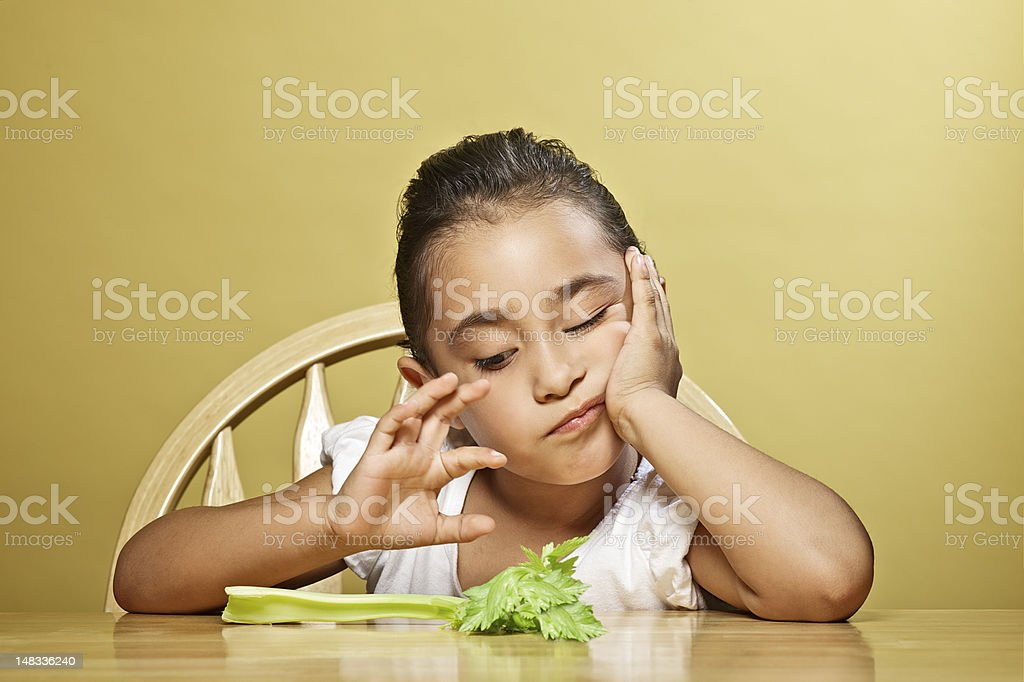 Young child making face at celery royalty-free stock photo
