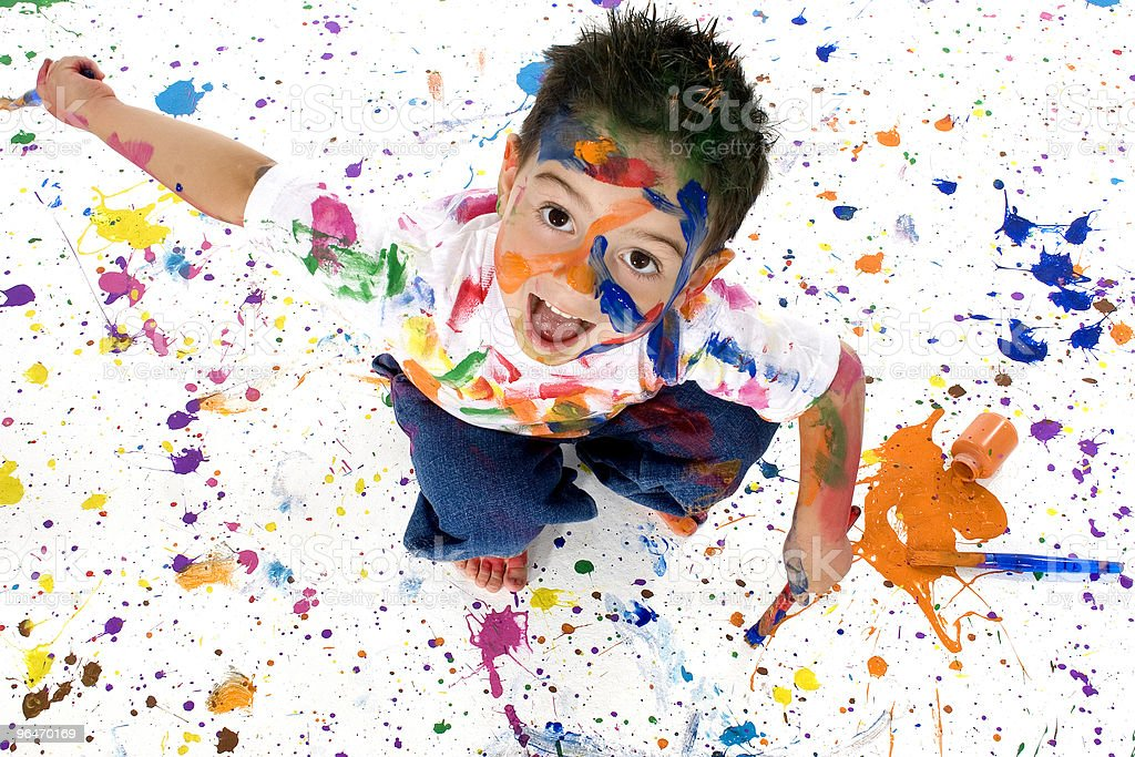 Young child on white floor covered in multicolored paint royalty-free stock photo