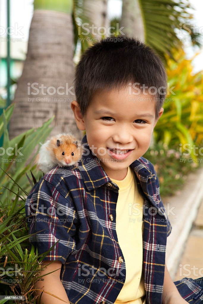 Young child outdoors with pet hamster stock photo