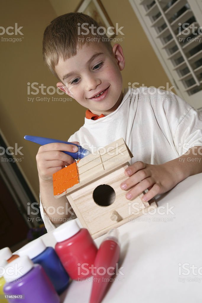 Young Child Painting a Bird House royalty-free stock photo