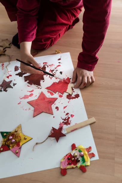 junges kind malen weihnachtsschmuck kniete auf dem boden - weihnachtsbilder zum ausmalen stock-fotos und bilder