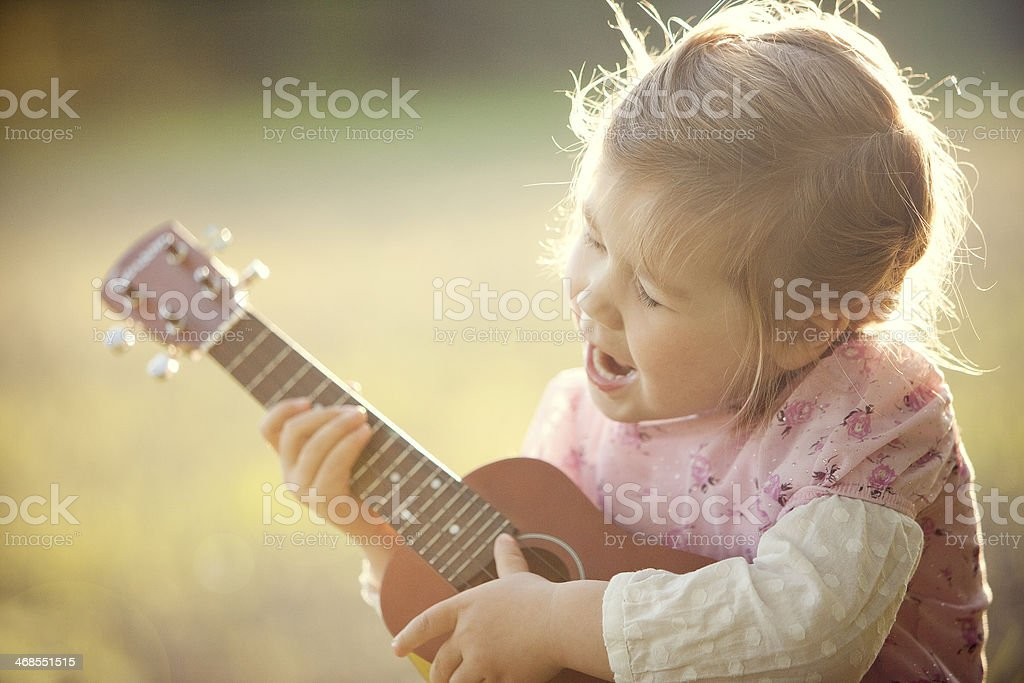 A young child playing a ukulele in the sunlight in a field stock photo