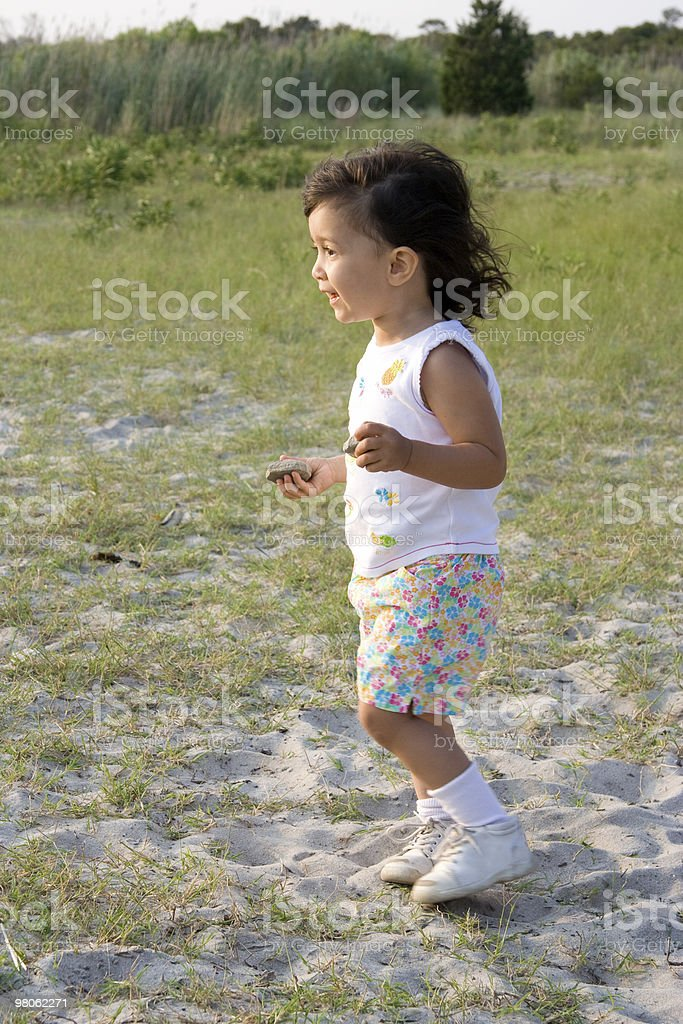 Young Child Playing on Grassy Beach royalty-free stock photo