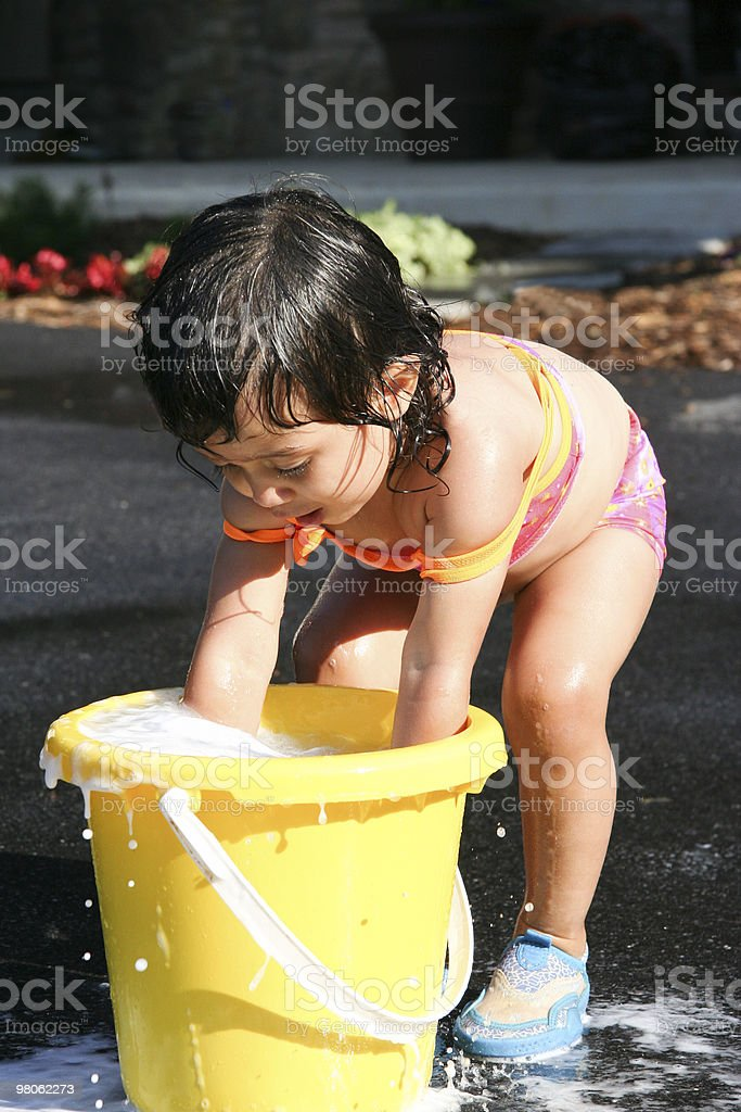 Young child playing with bucket of soap bubbles royalty-free stock photo