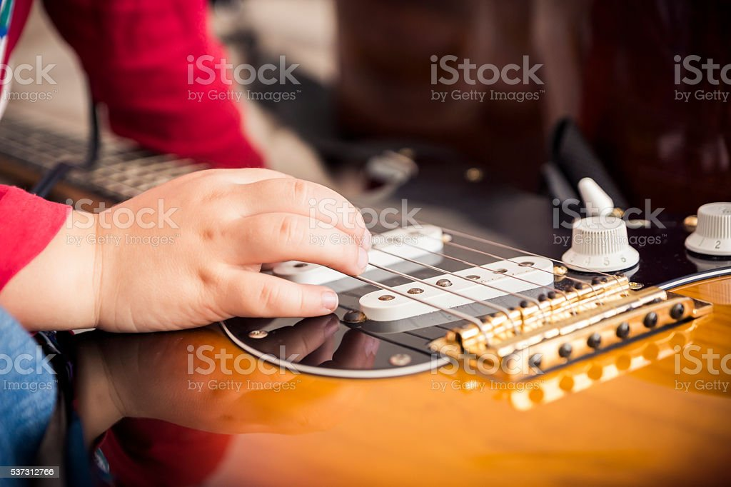 Young Child Playing with Guitar stock photo