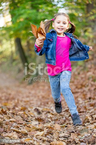 Young Child Running in Autumn with Big Smile - Stock Photo