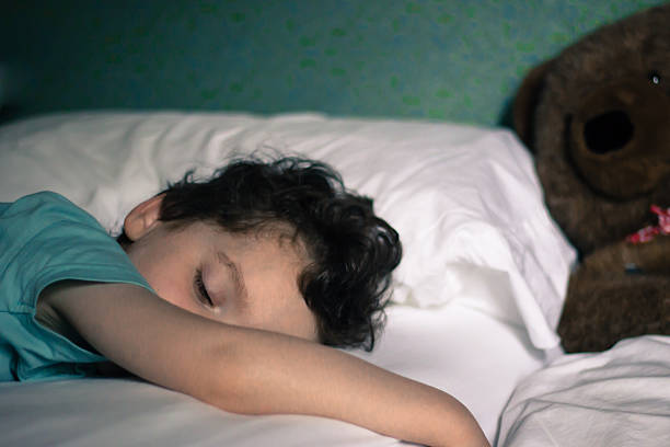 Young child sleeping in bed with teddy in background stock photo