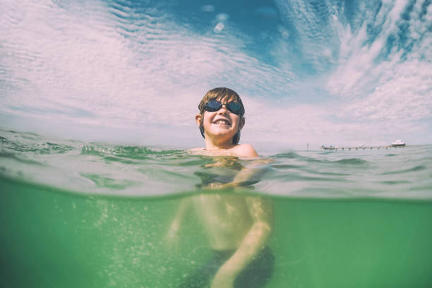 Young child swims in beautiful green waters of Florida stock photo