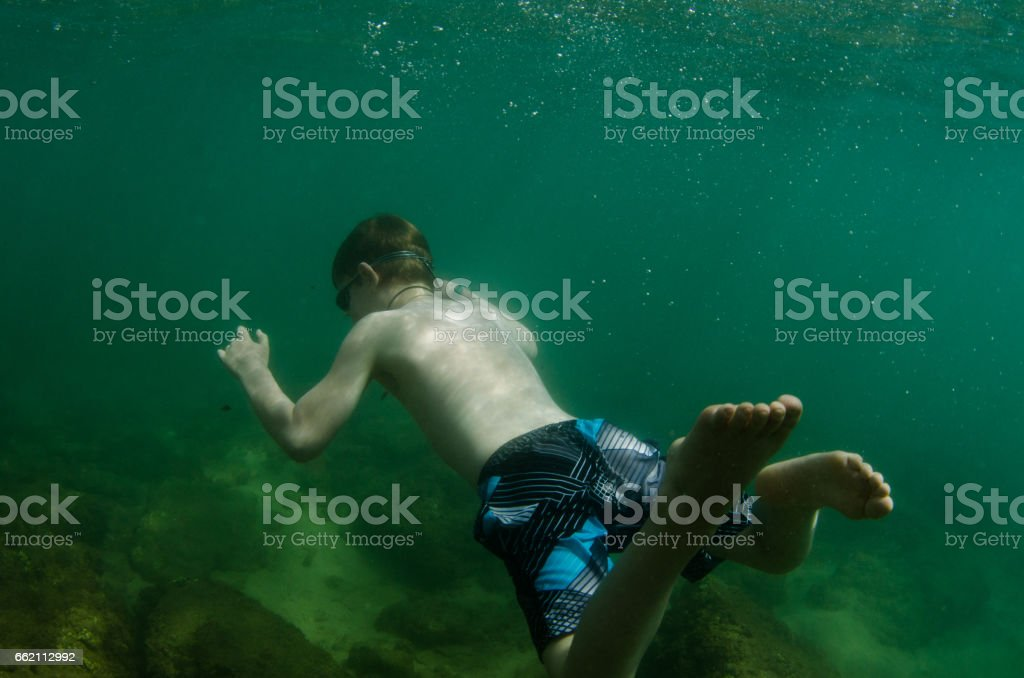 Young child swims in deep green waters of Kauai, Hawaii royalty-free stock photo