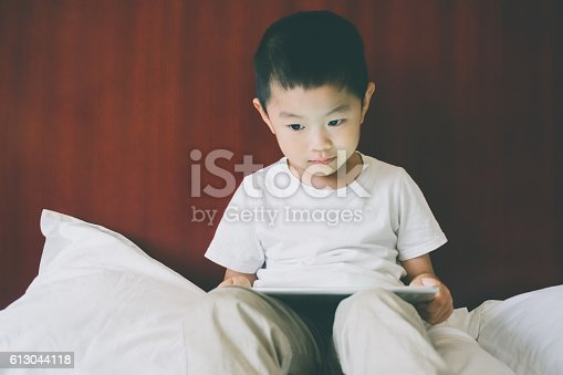 Young child using digital tablet in bed