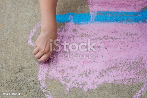 istock Young child using sidewalk chalk to draw a butterfly 1249019201