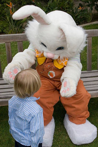 young child walking up to easter bunny - easter bunny stock photos and pictures