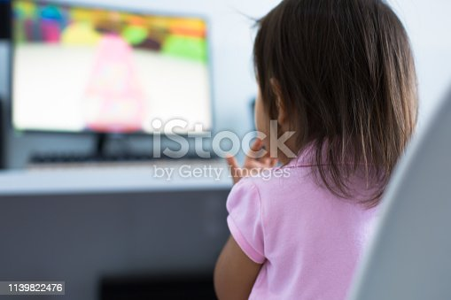 istock Young child watching tv on the computer at home 1139822476