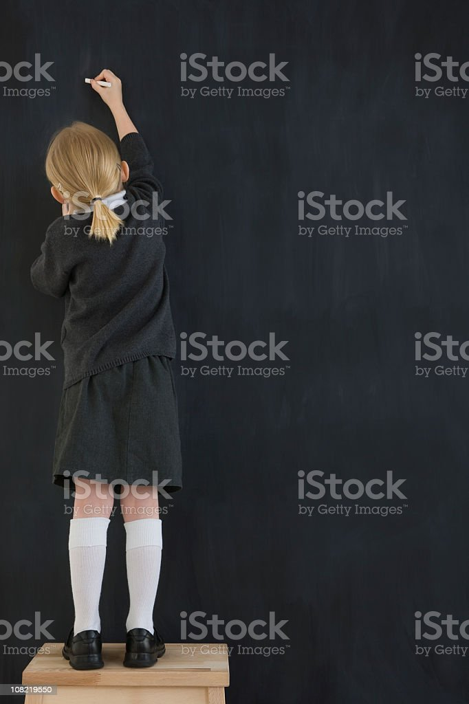 Young child writing on a chalkboard stock photo