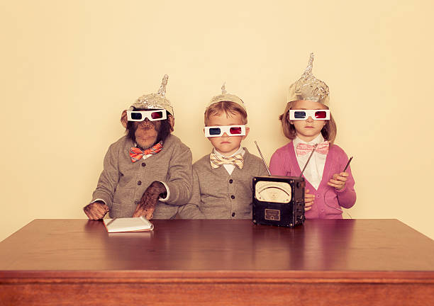 Young Children and Chimpanzee wear Tinfoil Hats A group of friends and their chimpanzee are trying to communicate with higher intelligence. 3 d glasses stock pictures, royalty-free photos & images