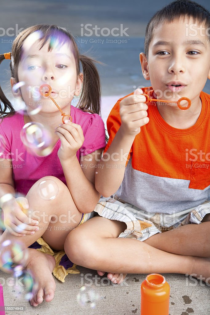 Young children blowing bubbles outside royalty-free stock photo