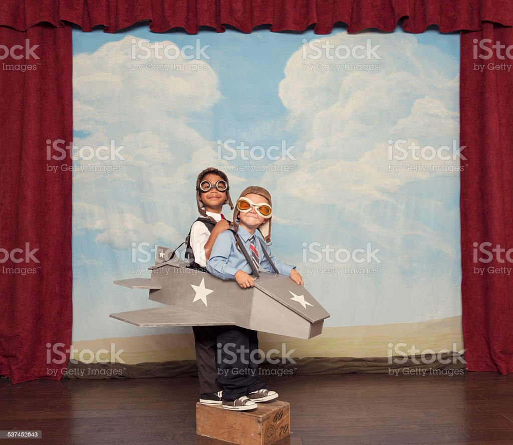 Young Children Dressed as Busnissmen in Toy Airplane stock photo
