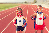 Boy and girl superheroes train to be the fastest superheroes on the planet. Image taken on a running track. The children are dressed up in masks and capes.