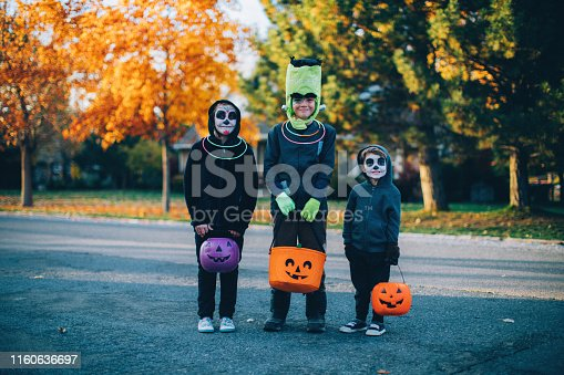 Three young children, two boys and one girl, are dressed as skeletons and Frankenstein for Halloween. They are ready to trick or treat for candy in a local residential neighborhood. Image taken in Utah, USA.