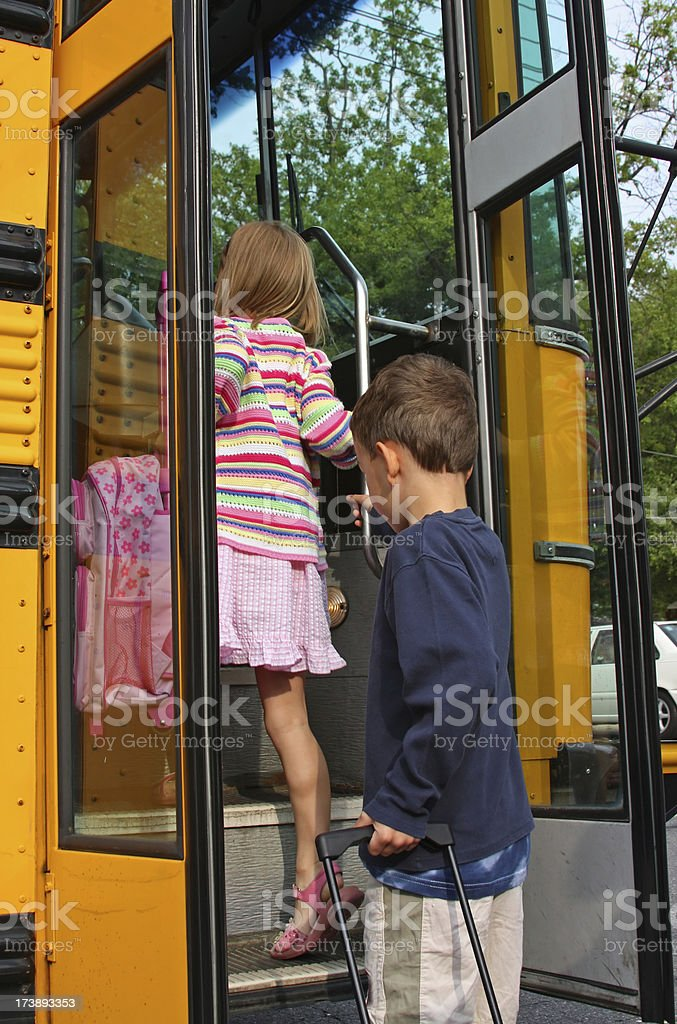 Young children getting into the schoolbus (USA) stock photo