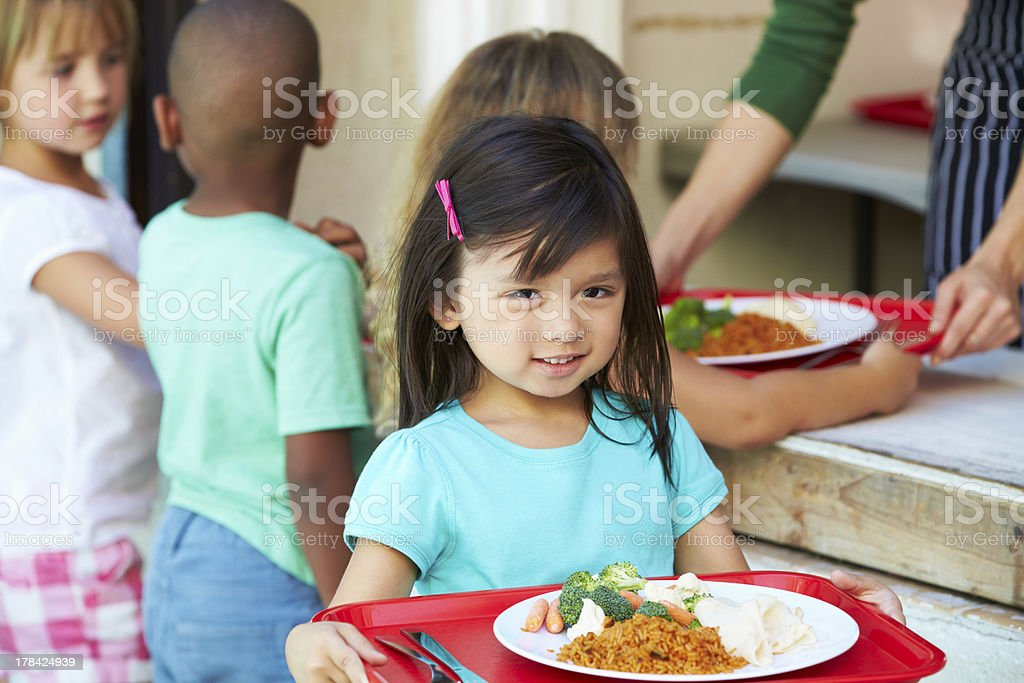 Young children getting lunch in a school cafeteria stock photo
