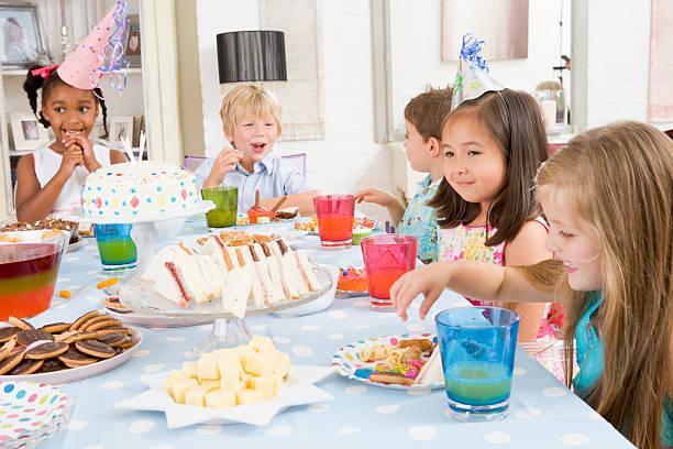 junge kinder, auf party sitzen am tisch mit essen lächeln - esszimmer buffet stock-fotos und bilder