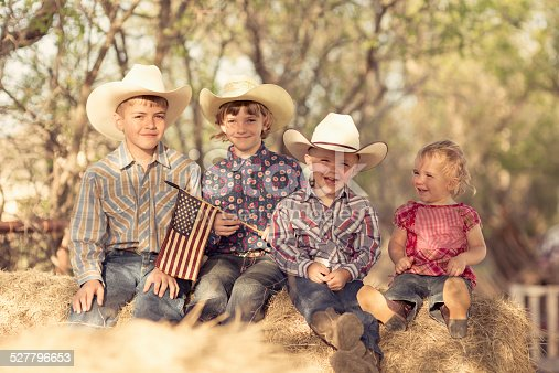 Young children pose for a portrait on their farm in Texas, USA.