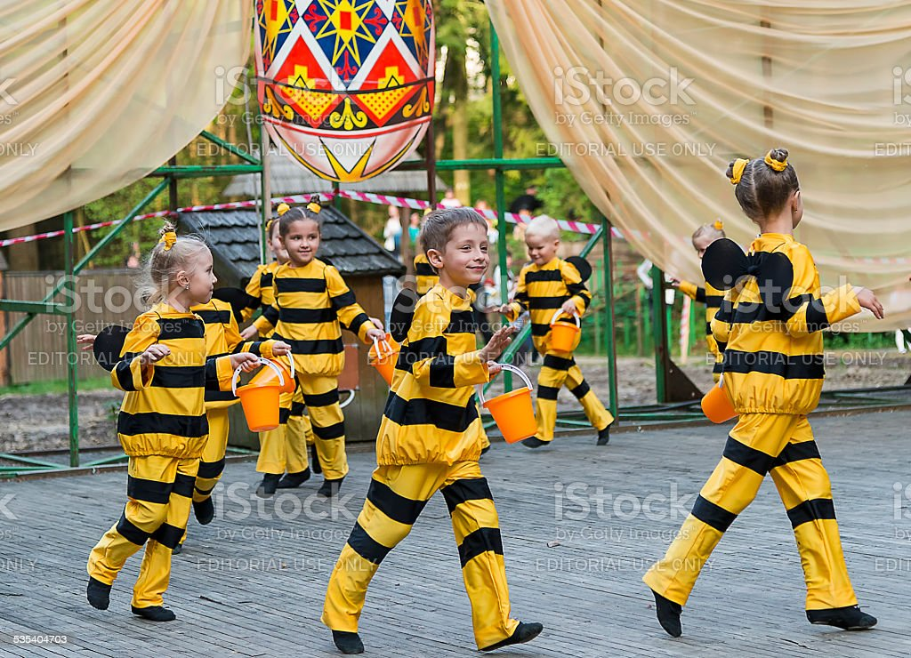 Young children perform on stage in costume bee stock photo