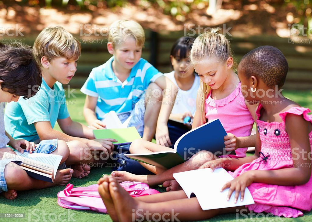 Young children sitting on grass and studying royalty-free stock photo