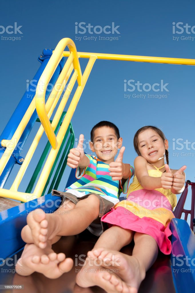 Young children sliding down the slide stock photo